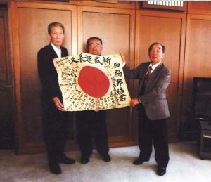 日章旗の返還を受けた西脇公一さん(中央)