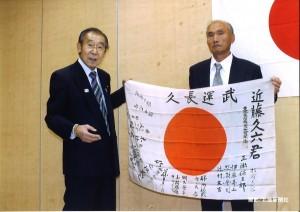 仲沢誠也本会常務理事から日章旗を受け取るご遺族の小畑久男さん(右)=5月11日、大館市中央公民館で