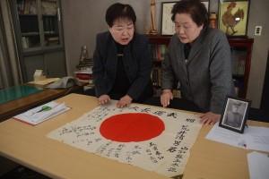 阿部博子山形県遺族会副会長から日章旗を受け取った荒井菊子さん(右)