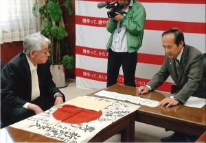 日章旗を神谷学・安城市長から受け取った本田紘さん(左)