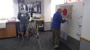 寄せられた日章旗を高画質撮影し記録するボランティアスタッフ