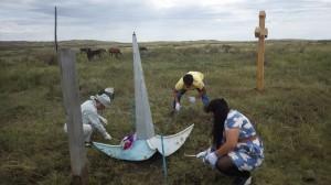 放置されている慰霊碑を清掃する派遣団=カザフスタン共和国カラカンダ州カラバス村で