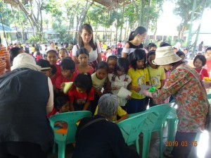 ネグロス島の小学校を訪問し生徒に折り紙を教える団員