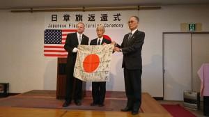 日章旗を持つアームストロングさん(左)、三木さんと伊藤さん