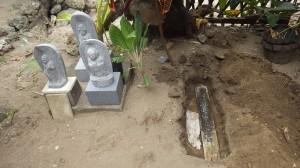シラッド村で倒壊した木製十字架を地蔵尊の傍らに埋設