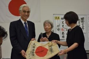 真鍋賢二会長(左端)より日章旗を受け取り喜びを語る大西さん(中央)