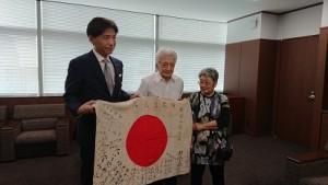 一宮市役所で、中野市長から日章旗を受け取る隆光さんと妻の和美さん