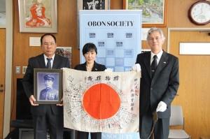甥の永澤秋高さん(左端)にOBONソサエティ代表から日章旗が引き渡された。=静岡県で