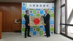 知多市役所で宮島市長から日章旗を受け取る勝則さん(右)