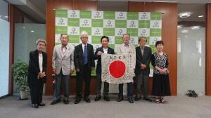 愛知県田原市田原福祉センターで日章旗を受け取った甥の喜孝さん(右から3人目)