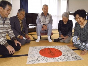 陸前高田市遺族会高田支部の皆さんへ日章旗を披露する津恵子さん(右端)