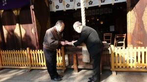 日章旗を受け取る甥の岡本明さん(左)